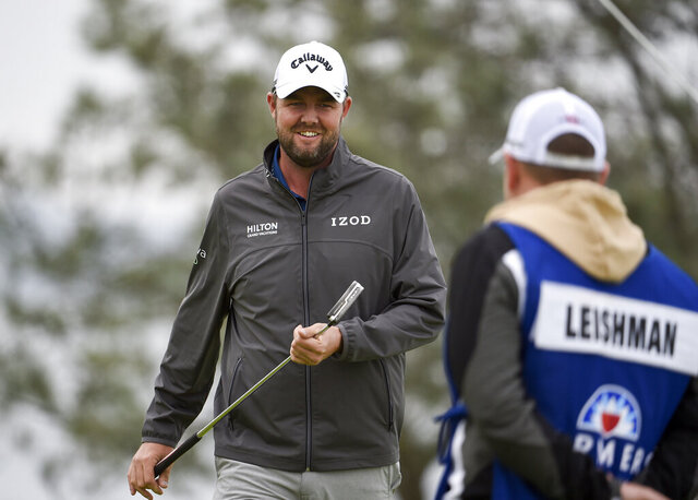 Marc Leishman, of Australia, smiles after putting on the fourth hole of the South Course at Torrey Pines Golf Course during the final round of the Farmers Insurance golf tournament Sunday, Jan. 26, 2020, in San Diego. (AP Photo/Denis Poroy)
