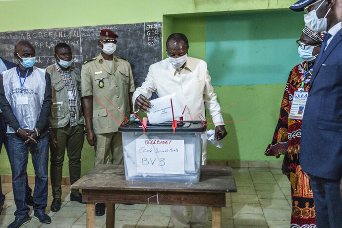 Guinean President Alpha Conde casts his ballot in Conakry, Guinea, Sunday Oct. 18, 2020. Guinean President Alpha Conde is seeking to extend his decade in power, facing off against his longtime rival Cellou Dalein Diallo for the third time at the polls. (AP Photo/Sadak Souici)