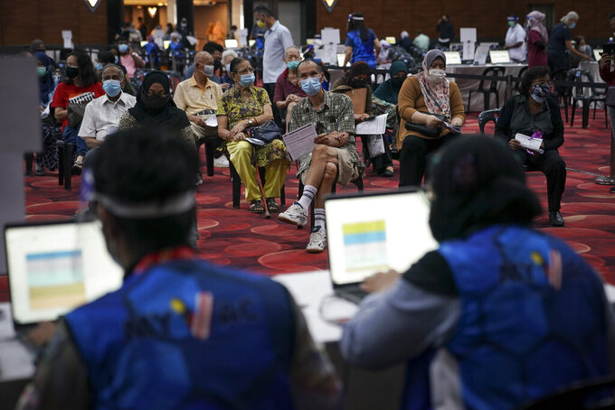 People wait to receive the Pfizer vaccine for the coronavirus at a vaccination center in Subang Jaya, Malaysia, Tuesday, April 27, 2021. (AP Photo/Vincent Thian)