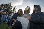 People pose with a newly unveiled statue of the mysterious developer of the Bitcoin digital currency in Budapest, Hungary, Thursday, Sept. 16, 2021. A bronze statue was unveiled in Hungary's capital on Thursday which its creators say is the first in the world to pay homage to the anonymous creator of the Bitcoin digital currency. Erected in a business park near the Danube River in Budapest, the bust sits atop a stone plinth engraved with the name of Satoshi Nakamoto, the pseudonym of the mysterious developer of Bitcoin whose true identity is unknown. (AP Photo/Bela Szandelszky)