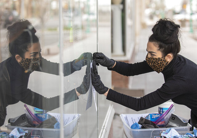 Small business owner, Liyah Babayan tapes up a sign while getting set up to donate masks to those that need them Monday, April 6, 2020, on Main Avenue in Twin Falls, Idaho. Babayan and her family spent three days making around 200 masks to give out to the community, though donations are encouraged so they can continue to make masks. (Drew Nash/Times-News via AP)