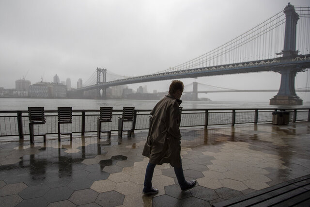A man walk alone on the promenade under the FDR drive in Lower Manhattan, Sunday, March 29, 2020. The new coronavirus causes mild or moderate symptoms for most people, but for some, especially older adults and people with existing health problems, it can cause more severe illness or death. (AP Photo/Mary Altaffer)