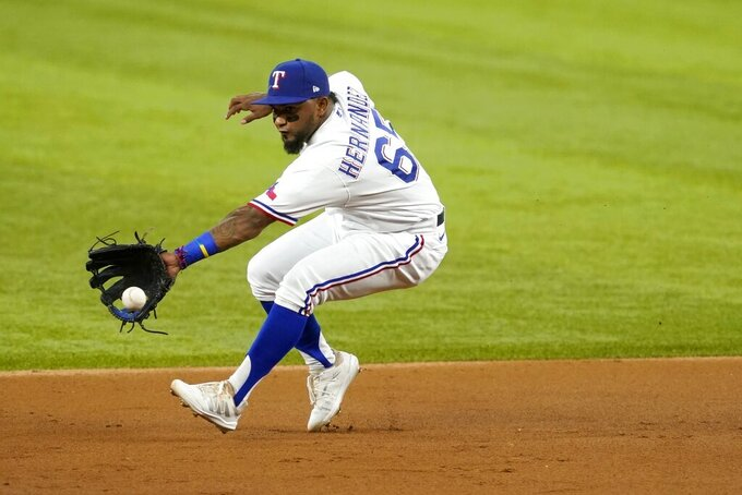 Texas Rangers third baseman Yonny Hernandez makes a play on a grounder by Seattle Mariners' Jake Fraley during the second inning of a baseball game in Arlington, Texas, Tuesday, Aug. 17, 2021. Kyle Seager was out at second on the play, and Fraley was safe at first. (AP Photo/Tony Gutierrez)