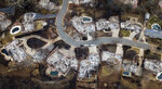 FILE - This Dec. 3, 2018, file photo, shows homes leveled by the Camp Fire line Valley Ridge Drive in Paradise, Calif. Attorneys representing 14 local governments said Tuesday, June 18, 2019, that they had reached a $1 billion settlement with California utility Pacific Gas & Electric for a series of fires dating to 2015. (AP Photo/Noah Berger, File)