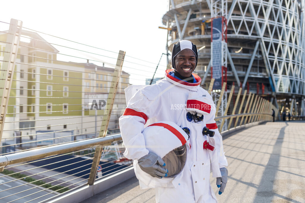 Smiling male astronaut holding space helmet while standing on bridge in city