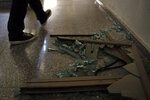A man passes broken glass inside the building that houses Hezbollah's media office in a stronghold of the Lebanese Hezbollah group in a southern suburb of Beirut, Lebanon, Sunday, Aug. 25, 2019. Two Israeli drones crashed in a Hezbollah stronghold in the Lebanese capital overnight without the militants firing on them, a spokesman for the group said Sunday, saying the first fell on the roof of a building housing Hezbollah's media office while the second landed in a plot behind it. (AP Photo/Bilal Hussein)