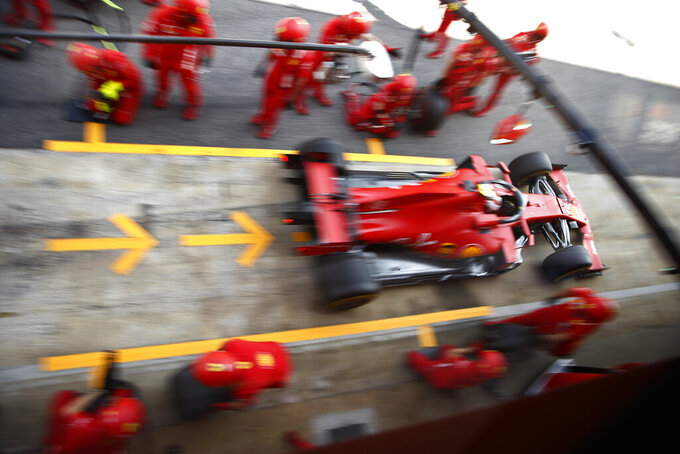 Ferrari driver Sebastian Vettel of Germany drives out of the pits after changing tyres during the second practice session prior to the Formula One Grand Prix at the Barcelona Catalunya racetrack in Montmelo, Spain, Friday, Aug. 14, 2020. (AP Photo, Emilio Morenatti, Pool)