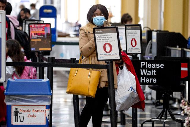 A woman wearing a mask walks goes through security at Ronald Reagan Washington National Airport, Monday, March 16, 2020, in Arlington, Va. (AP Photo/Andrew Harnik)