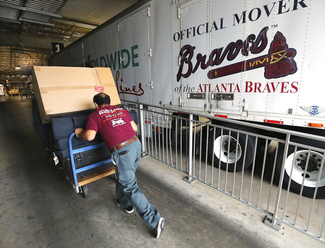 An employee from Atlanta Peach Movers, loads baseball equipment, Tuesday, Feb. 4, 2020, in Atlanta, as the Atlanta Braves prepare to depart for spring training. Braves pitchers and catchers will report to the team's new spring training home in North Port, Fla., on Wednesday, Feb. 12. (Curtis Compton/Atlanta Journal-Constitution via AP)