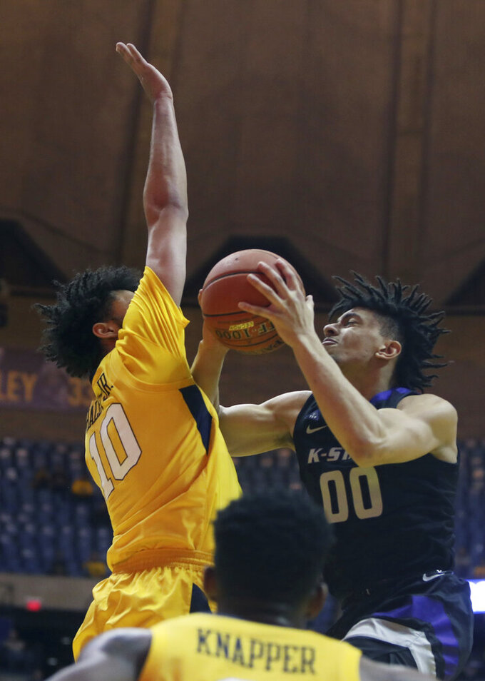 Kansas State guard Mike McGuirl (00) drives to the basket while defended by West Virginia guard Jermaine Haley (10) during the first half of an NCAA college basketball game Monday, Feb. 18, 2019, in Morgantown, W.Va. (AP Photo/Raymond Thompson)