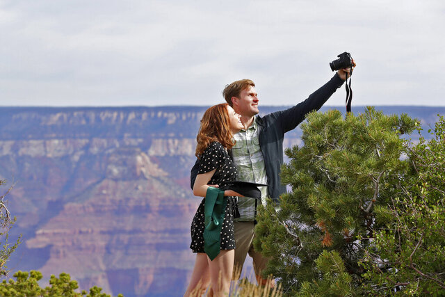 Recent Baylor University graduate Cady Malachowski takes a photo with Andrew Fink at the Grand Canyon Friday, May 15, 2020, in Grand Canyon, Ariz. Tourists are once again roaming portions of Grand Canyon National Park when it partially reopened Friday morning, despite objections that the action could exacerbate the coronavirus pandemic.. (AP Photo/Matt York)