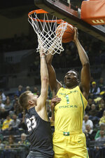 Oregon's N'Faly Dante, right, goes up for a shot over Montana's Mack Anderson during the first half of an NCAA college basketball game in Eugene, Ore., Wednesday, Dec. 18, 2019. (AP Photo/Chris Pietsch)