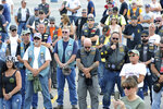 People stand in silence during a memorial and remembrance service for seven motorcyclists and their spouses who died in the June crash, Saturday, July 13, 2019 in the parking lot of Gillette Stadium in Foxboro, Mass. The seven bikers were killed when a pickup truck hauling a flatbed trailer slammed into a group of riders in Randolph, New Hampshire.  (Mark Stockwell/The Sun Chronicle via AP)
