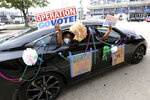 FILE - In this Oct. 24, 2020, file photo, participants drive past the Smoothie King Center, which has been converted to an early voting location, at the end of a