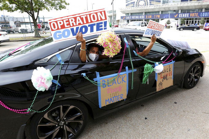 """FILE - In this Oct. 24, 2020, file photo, participants drive past the Smoothie King Center, which has been converted to an early voting location, at the end of a """"Parade to the Polls"""" event, organized by Operation Go Vote!, a collaborative of African American civic and social organizations, in New Orleans. Several years since its founding, BLM has evolved well beyond the initial aspirations of its early supporters. Now, its influence faces a test, as voters in the Tuesday, Nov. 3 general election choose or reject candidates who endorsed or denounced the BLM movement amid a national reckoning on race. (AP Photo/Rusty Costanza)"""