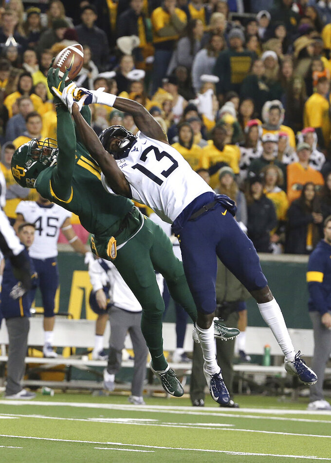 Baylor cornerback Jameson Houston (11) breaks up the pass intended for West Virginia wide receiver Sam James (13) during the second half of an NCAA college football game in Waco, Texas, Thursday, Oct. 31, 2019. Baylor won 17=14. (AP Photo/Jerry Larson)