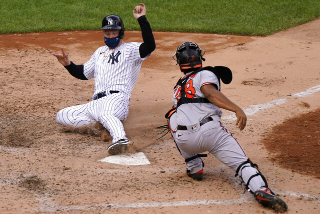 New York Yankees Clint Frazier, left, is safe scoring ahead of the tag by Baltimore Orioles catcher Pedro Severino (28) on pinch-hitter Gleyber Torres's two-run double during the eighth inning of a baseball game, Sunday, Sept. 13, 2020, at Yankee Stadium in New York. (AP Photo/Kathy Willens)
