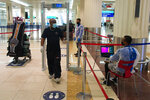 FILE - In this June 10, 2020 file photo, passenger wearing a mask due to the coronavirus pandemic passes through a temperature screening at Dubai International Airport's Terminal 3 in Dubai, United Arab Emirates. Hundreds of thousands of foreign residents of the UAE are struggling to return to the country after a lockdown over the coronavirus. They left behind jobs, families, homes and other responsibilities of which they always planned to return. But some tell The Associated Press they still face challenges in trying to come back. (AP Photo/Jon Gambrell, File)