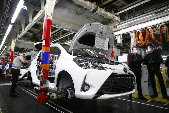 FILE - In this April 28, 2020, file photo, an employee wearing a face mask works on a Yaris car at the Toyota car factory in Onnaing, northern France. Toyota announced Thursday, Aug. 19, 2021, is scaling back 40% of its production, affecting 14 auto assembly plants in Japan, as the surging coronavirus pandemic in southeast Asia crimps the parts supply. (AP Photo/Michel Spingler, File)