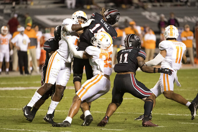 Tennessee's Will Brooks (35) and Deandre Johnson (13) converge on South Carolina quarterback Collin Hill (15) during the second half of an NCAA college football game Saturday, Sept. 26, 2020, in Columbia, S.C. (AP Photo/Sean Rayford)