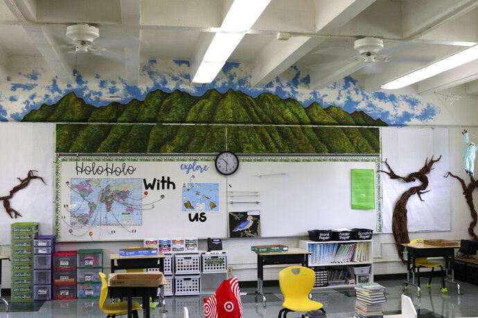 Desks are spaced out in a classroom at Aikahi Elementary School in Kailua, Hawaii on Tuesday, July 28, 2020. While Hawaii has one of the lowest rates of cases per capita in the country and many of its schools have open-air campuses, the challenges of returning kids full time to classrooms may still be insurmountable. (AP Photo/Jennifer Sinco Kelleher)