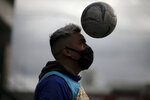 Martin Rodriguez eyes the ball as he warms up prior to an amateur soccer match at the Play Futbol 5 local club in Pergamino, Argentina, Wednesday, July 1, 2020. The club divided its soccer field into 12 rectangles to mark limited areas for each player, keeping them from making physical contact, an adaptation to continue playing amid government restrictions to curb the spread of the new coronavirus.  (AP Photo/Natacha Pisarenko)