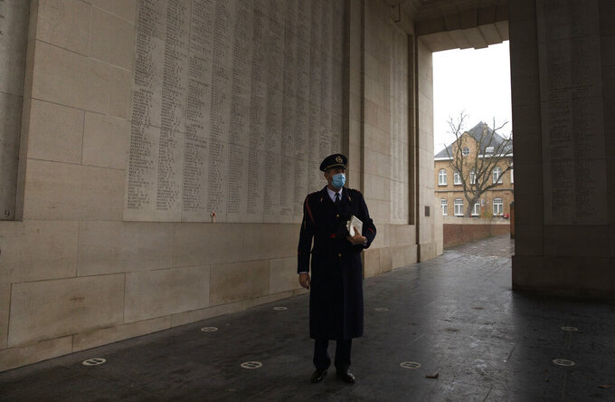 Last Post bugler Tonny Desodt stands on social distancing markers at the Menin Gate Memorial to the Missing prior to an Armistice Day ceremony in Ypres, Belgium, Wednesday, Nov. 11, 2020. In a town usually crowded with visitors, coronavirus restrictions prevented the general public from attending a ceremony under the Menin Gate, with even dignitary attendance reduced to a minimum. (AP Photo/Virginia Mayo)