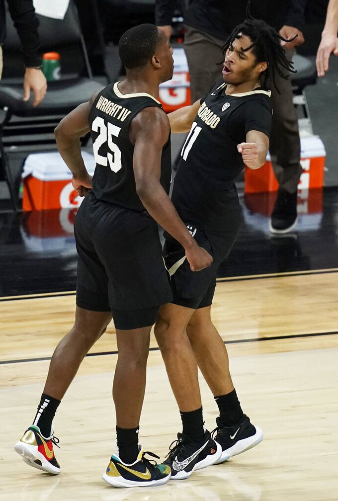 Colorado's McKinley Wright IV (25) and Keeshawn Barthelemy (11) celebrate after a play against Southern California during the first half of an NCAA college basketball game in the semifinal round of the Pac-12 men's tournament Friday, March 12, 2021, in Las Vegas. (AP Photo/John Locher)