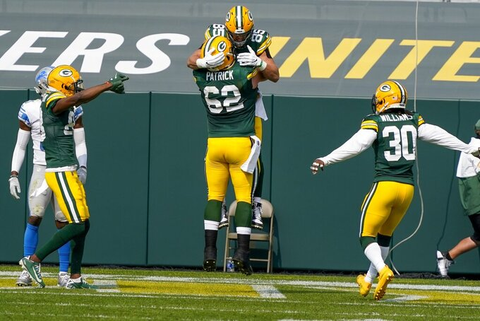 Green Bay Packers' Robert Tonyan is congratulated by Lucas Patrick (62) after catching a touchdown pass during the first half of an NFL football game against the Detroit Lions Sunday, Sept. 20, 2020, in Green Bay, Wis. (AP Photo/Morry Gash)