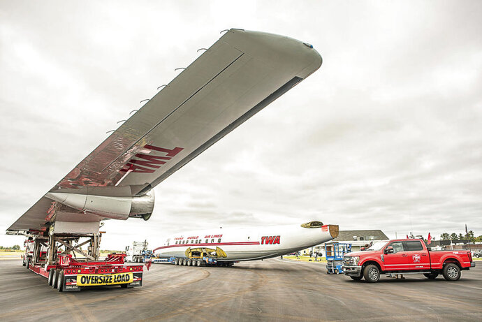 This photo shows A vintage commercial airplane at the Auburn-Lewiston Airport in Auburn, Maine, Monday, Oct. 8, 2018. The wings, body and tail of the rare Super Star aircraft will be joining a nearly one mile long convoy to JFK airport to become a part of the TWA hotel. (Andree Kehn/Sun Journal via AP)