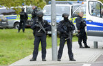Police officers block a road in Halle, Germany, Wednesday, Oct. 9, 2019. One or more gunmen fired several shots on Wednesday in the German city of Halle. Police say a person has been arrested after a shooting that left two people dead. (AP Photo Jens Meyer)