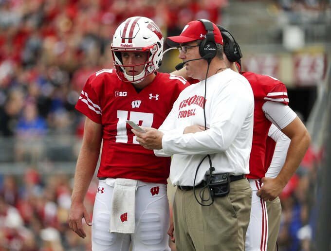 Wisconsin head coach Paul Chryst talks to quarterback Jack Coan during the first half of an NCAA college football game against Central Michigan Saturday, Sept. 7, 2019, in Madison, Wis. (AP Photo/Morry Gash)