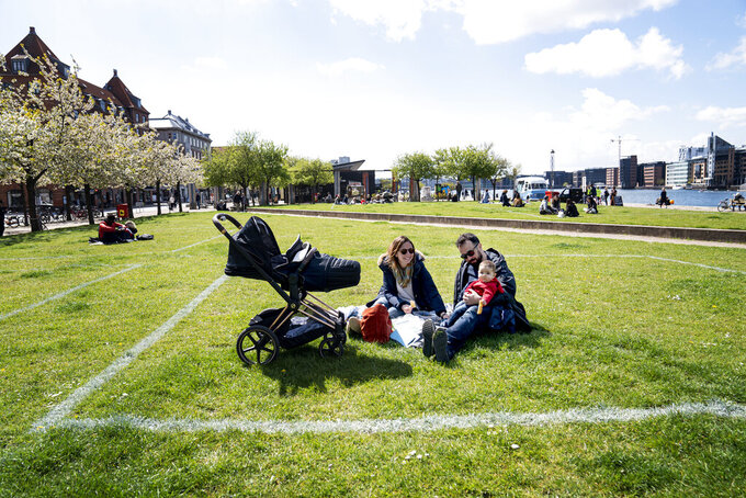 Marina and Andrea enjoy the sun with their daughter Sara at Islands Brygge in Copenhagen on Sunday, May 3, 2020. Marked areas on the grassland help people keep distance from each other, with about 40 m2 area marked out for a maximum of 10 people, to limit the spread of coronavirus infection, seen with 24 mm telephoto lens. (Ida Guldbaek Arentsen / Scanpix via AP)