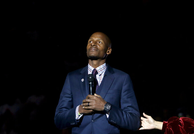 Naismith Memorial Basketball Hall of Famer Ray Allen holds a microphone as his number is retired to the rafters during a halftime ceremony at an NCAA college basketball game between South Florida and Connecticut, Sunday, March 3, 2019, in Storrs, Conn. (AP Photo/Steven Senne)