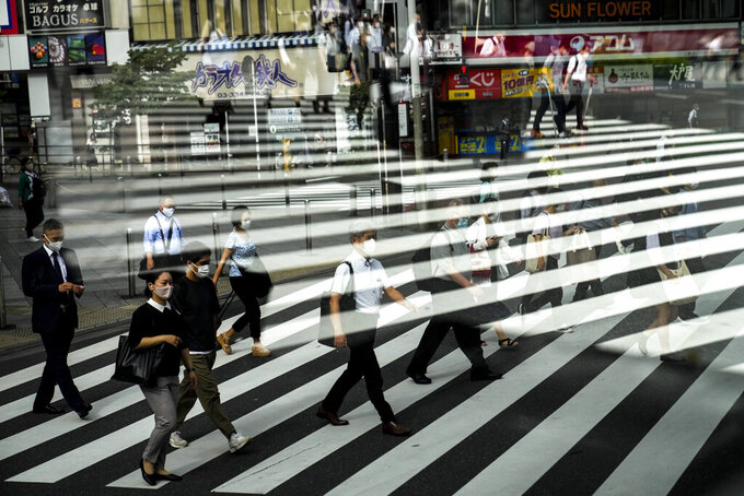 Commuters are reflected in a bus window as they cross the street Thursday, July 15, 2021, in Tokyo. The pandemic-delayed 2020 Summer Olympics open on July 23 without spectators at most venues. (AP Photo/Jae C. Hong)