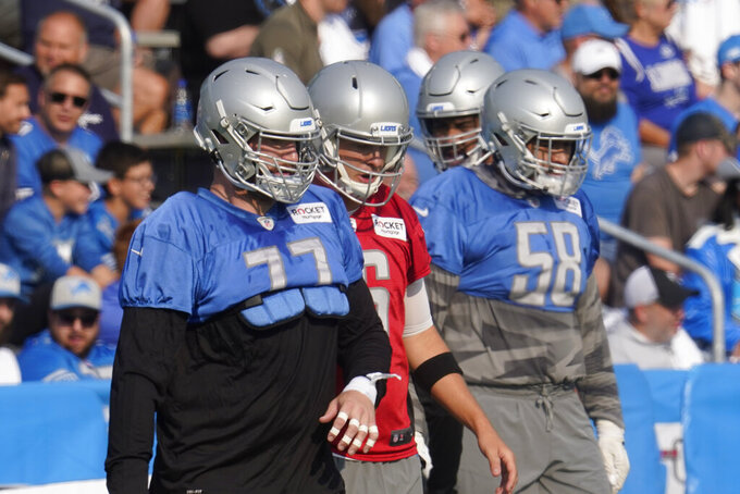 Detroit Lions offensive guard Frank Ragnow (77), quarterback Jared Goff (16) and offensive tackle Penei Sewell (58) warm up during an NFL football training camp practice in Allen Park, Mich., Saturday, July 31, 2021. (AP Photo/Paul Sancya)
