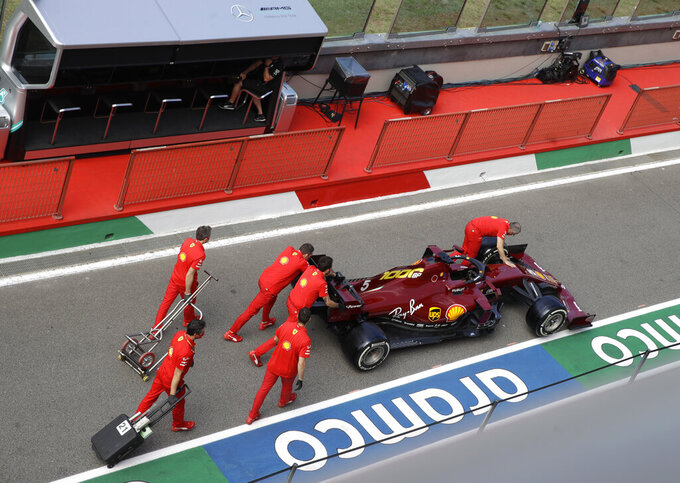 Pit crew wheel the car of Ferrari driver Sebastian Vettel of Germany at the Mugello circuit, in Scarperia, Italy, Thursday, Sept. 10, 2020, ahead of Sunday's Formula One Grand Prix of Tuscany. The car was presented with a new color on Thursday to mark Ferrari's 1,000th GP. (AP Photo/Luca Bruno)