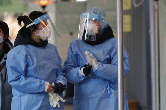 Medical workers wearing protective gears in the sub-zero temperatures talk at coronavirus testing site in Seoul, South Korea, Monday, Dec. 21, 2020. (AP Photo/Lee Jin-man)
