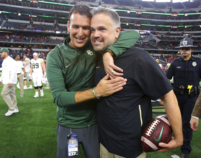 FILE - In this Nov. 24, 2018, file photo, Baylor athletic director Mack Rhoades, left, congratulates head coach Matt Rhule after defeating Texas Tech in an NCAA college football game, in Arlington, Texas. A person familiar with the situation says the Carolina Panthers are completing a contract to hire Baylor's Matt Rhule as their coach. The person spoke to The Associated Press on Tuesday, Jan. 7, 2020, on condition of anonymity because the deal is not done. The Panthers have not spoken publicly about the coaching search. (Jerry Larson/Waco Tribune-Herald via AP, File)