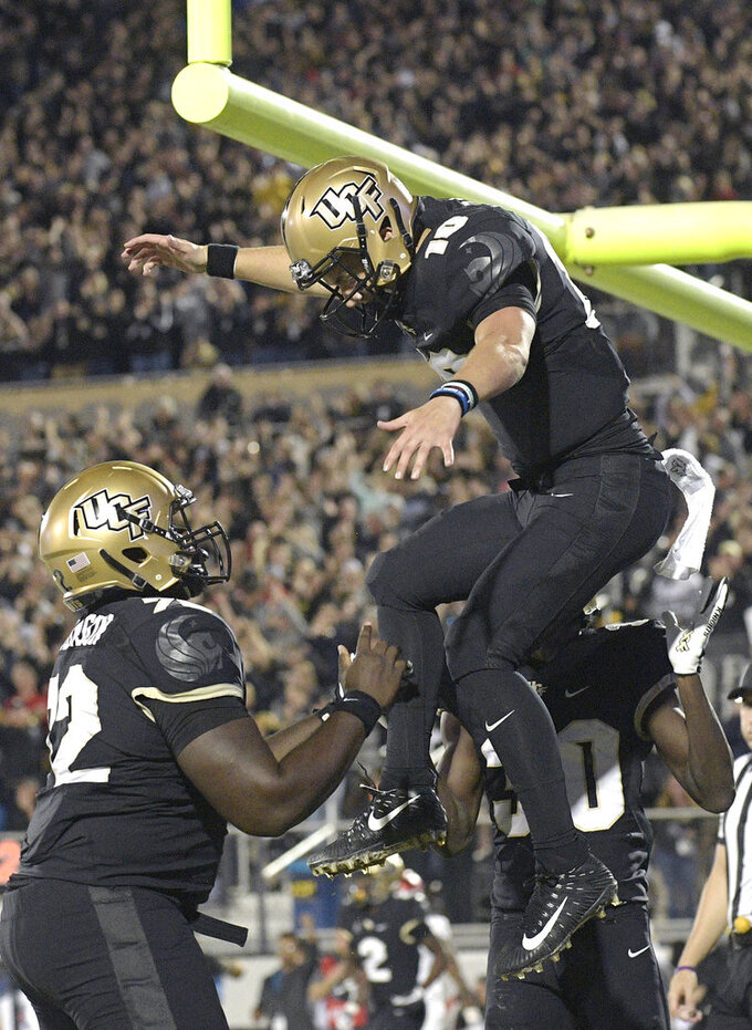Central Florida quarterback McKenzie Milton (10) celebrates with offensive lineman Jordan Johnson (72) and running back Greg McCrae (30) after Milton rushed for a 3-yard touchdown during the first half of an NCAA college football game against Cincinnati on Saturday, Nov. 17, 2018, in Orlando, Fla. (AP Photo/Phelan M. Ebenhack)