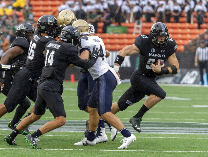 Hawaii defensive lineman Maxwell Hendrie (92) scoops up a blocked Navy punt and runs it in for a touchdown during the first half of an NCAA college football game Saturday, Sept. 1, 2018, in Honolulu. (AP Photo/Eugene Tanner)