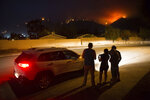 Residents who were evacuated use a phone to watch a surveillance camera of their house as the Holy Fire approaches on Thursday night, Aug. 9, 2018 in Temescal Valley, Calif.  More than a thousand firefighters battled to keep a raging Southern California forest fire from reaching foothill neighborhoods Friday before the expected return of blustery winds that drove the flames to new ferocity a day earlier. (AP Photo/Patrick Record)