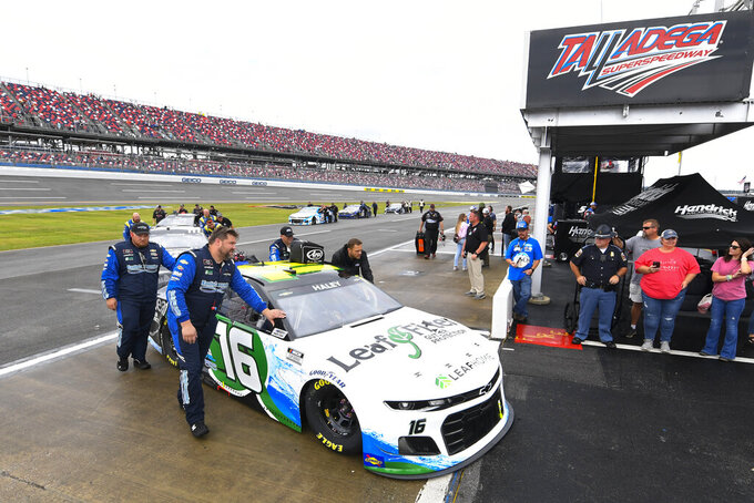 Team members, including Justin Haley's, push their cars out of pit row after a NASCAR Cup series auto race was postponed until Monday due to rain Sunday, Oct. 3, 2021, in Talladega, Ala. (AP Photo/John Amis)