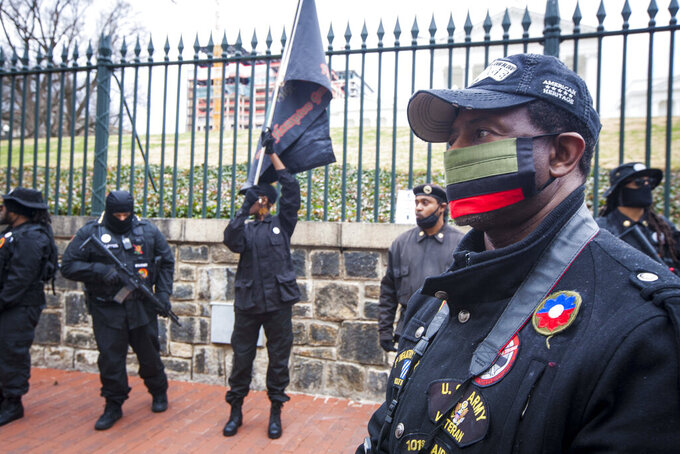Earl Lewis, manager of Black Lives Matter 757, stands in front of Capitol Square with members of the New Black Panther Party, The Fred Hampton Gun Club, and The Original Black Panthers of Virginia during Lobby Day in Richmond, Va. Monday Jan. 18, 2021. (AP Photo/John C. Clark)