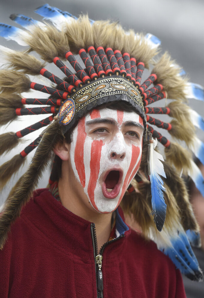 """FILE - In this May 20, 2015, file photo, a Cheyenne Mountain High School student wears a headdress and face paint as he cheers for his school -- which uses """"Indians"""" as its team mascot -- in the 4A State Soccer Championship game at Dick's Sporting Goods Park in Commerce City, Colo. The U.S. has spent most of 2019 coming to grips with blackface and racist imagery, including a racist photo on the Virginia governor's college yearbook page. But Native Americans say they don't see significant pressure applied to those who perpetuate Native American stereotypes. (Mark Reis/The Gazette via AP, File)"""