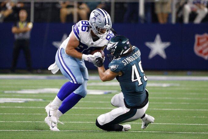 Dallas Cowboys tight end Dalton Schultz (86) catches a pass as Philadelphia Eagles linebacker Alex Singleton (49) makes the stop in the first half of an NFL football game in Arlington, Texas, Monday, Sept. 27, 2021. (AP Photo/Ron Jenkins)