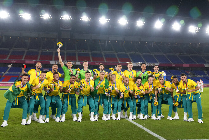 Players of Brazil pose with their gold medals after defeating Spain in the men's soccer final match at the 2020 Summer Olympics, Sunday, Aug. 8, 2021, in Yokohama, Japan. (AP Photo/Fernando Vergara)