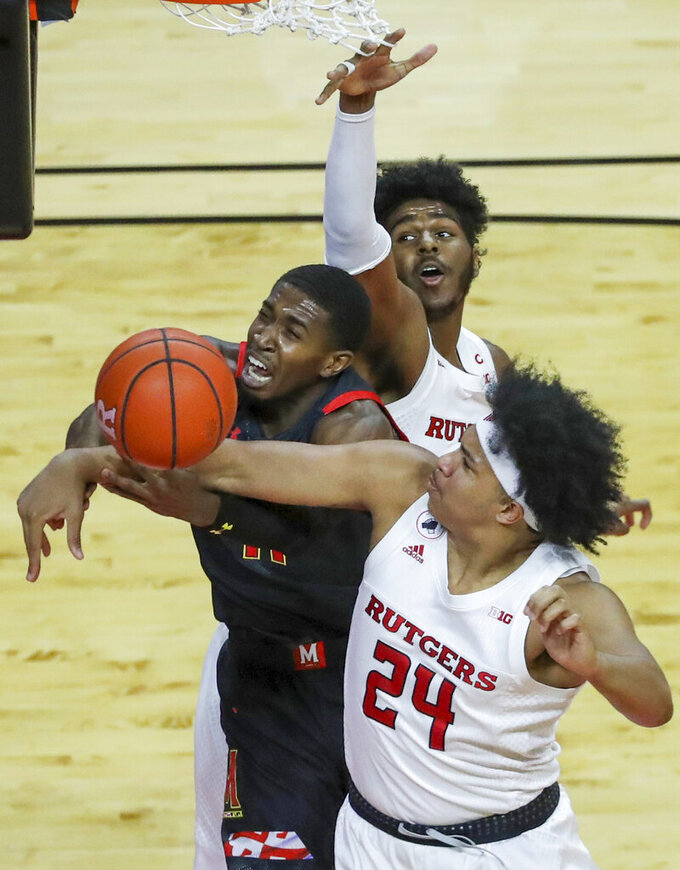 Maryland guard Darryl Morsell, center, is fouled by Rutgers guard Ron Harper Jr., right, as Rutgers center Myles Johnson, left,  defends during the first half of an NCAA college basketball game in Piscataway, N.J., Sunday, Feb. 21, 2021. (Andrew Mills/NJ Advance Media via AP)