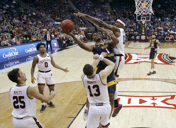 West Virginia's Derek Culver (1) shoots under pressure from Texas Tech's Tariq Owens (11) during the second half of an NCAA college basketball game in the Big 12 men's tournament Thursday, March 14, 2019, in Kansas City, Mo. West Virginia won 79-74. (AP Photo/Charlie Riedel)