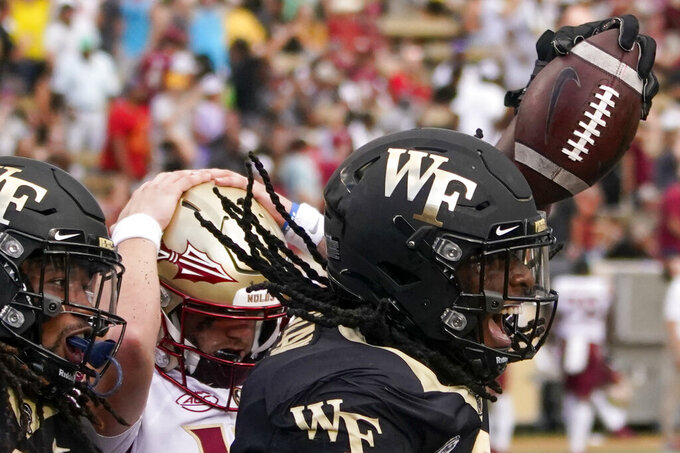 Wake Forest defensive lineman Luiji Vilain, right, celebrates after recovering a fumble in the end zone as Florida State quarterback McKenzie Milton, center, reacts during the second half of an NCAA college football game Saturday, Sept. 18, 2021, in Winston-Salem, N.C. (AP Photo/Chris Carlson)